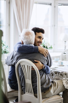 Young caretaker embracing senior male at nursing home - MASF02944