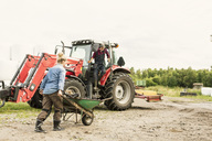 Woman pushing wheelbarrow towards man and tractor at farm - MASF02953