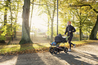 Woman jogging with baby stroller on road at park - MASF02956