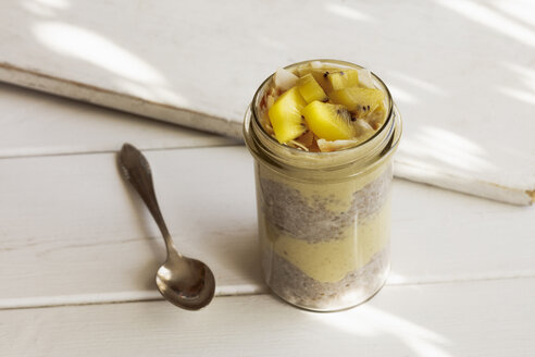 Glass of chia pudding with mango smoothie garnished with kiwi and coconut flakes - EVGF03357