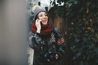 Portrait of laughing young woman with camera on the phone - OCAF00178