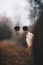 Woman's hand holding sunglasses - OCAF00187