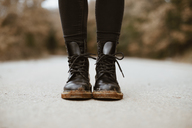 Woman wearing black boots, partial view - OCAF00196