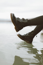 Woman wearing black boots touching water surface of lake, partial view - OCAF00199