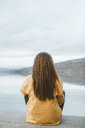 Back view of young woman sitting on jetty - OCAF00205