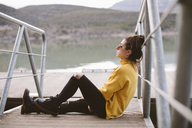 Pensive young woman relaxing on jetty - OCAF00208