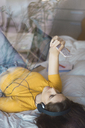 Young woman with headphones lying on bed taking selfie with smartphone - KKAF00975