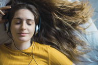 Portrait of smiling young woman lying on bed listening music with headphones - KKAF00978