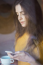 Portrait of young woman with coffee cup looking at cell phone - KKAF00981
