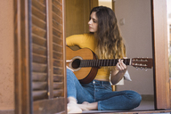 Young woman sitting on the floor at home playing guitar - KKAF00984
