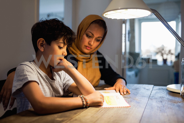 Mother and son reading book under illuminated desk lamp at home - MASF02981 - Maskot ./Westend61