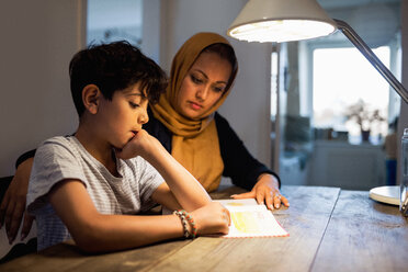 Mother and son reading book under illuminated desk lamp at home - MASF02981