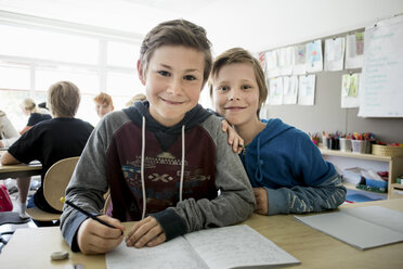 Portrait of happy boys with books sitting on desk at classroom - MASF02987