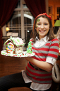 Portrait of smiling girl with face paint holding gingerbread house - CAVF36268