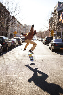 Man skateboarding on city street against clear sky - CAVF36301