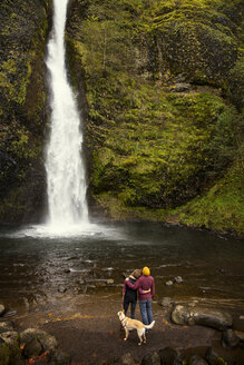 Rear view of couple with dog looking waterfall - CAVF36346