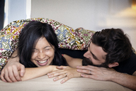 Happy couple talking while lying on bed at home - CAVF36358