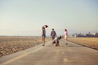 Friends skateboarding on road against clear sky - CAVF36382