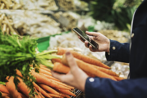 Midsection of woman using phone while buying carrots in supermarket - MASF03006
