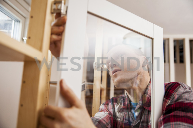 Mature male carpenter installing door for cabinet at home - MASF03012