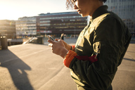 Midsection of teenage girl using phone on city street during sunny day - MASF03018