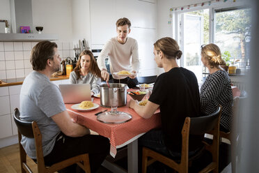 Man serving food for family at dining table - MASF03024