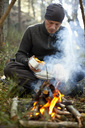 Man cooking chanterelle mushrooms at bonfire in forest - MASF03027