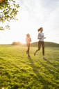 Mother and daughter running on grass at park against sky during sunset - MASF03030