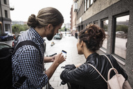 Man showing smart phone to friend on sidewalk in city - MASF03039