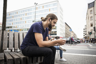 Man listening music through smart phone while sitting beside woman on wooden bench in city - MASF03042