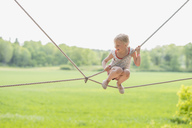 Happy girl sitting on ropes over field during sunny day - MASF03045