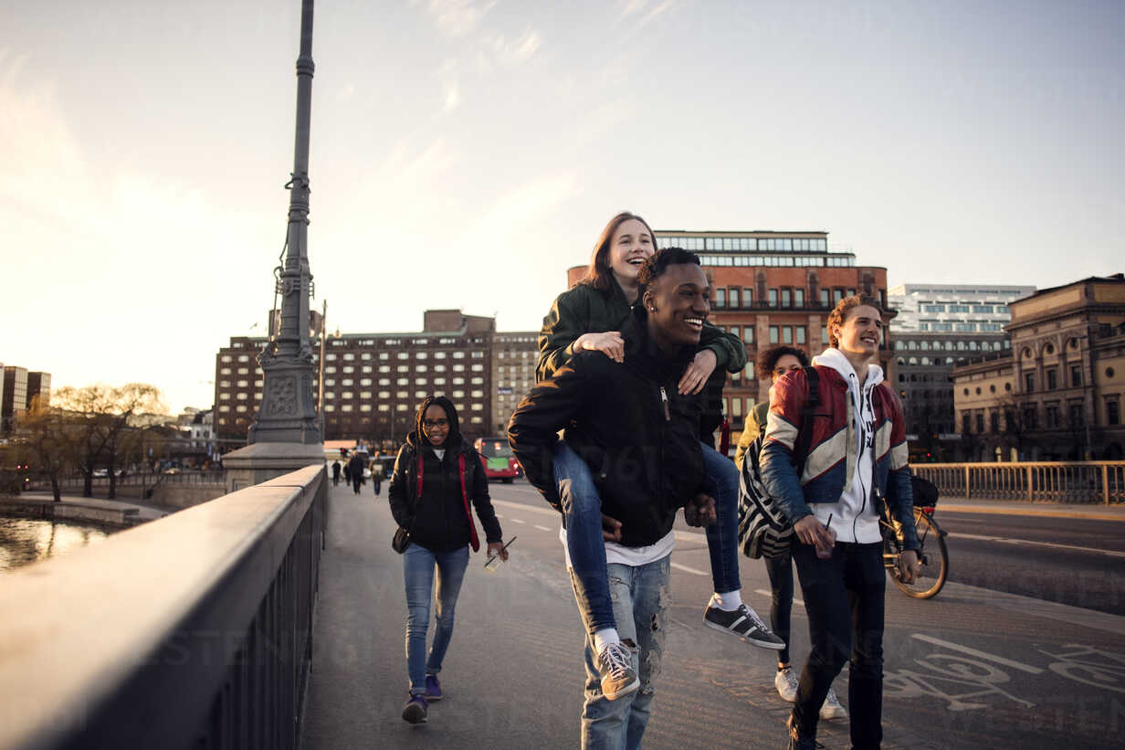 Happy teenage boy piggybacking friend while walking on bridge in city - MASF03048 - Maskot ./Westend61