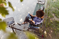 High angle view of businesswoman using digital tablet on park bench - MASF03069