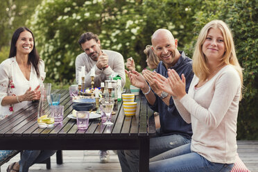 Happy family and friend applauding while sitting at dining table in back yard during garden party - MASF03084