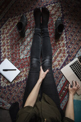 Low section of blogger using laptop while sitting on carpet - MASF03087