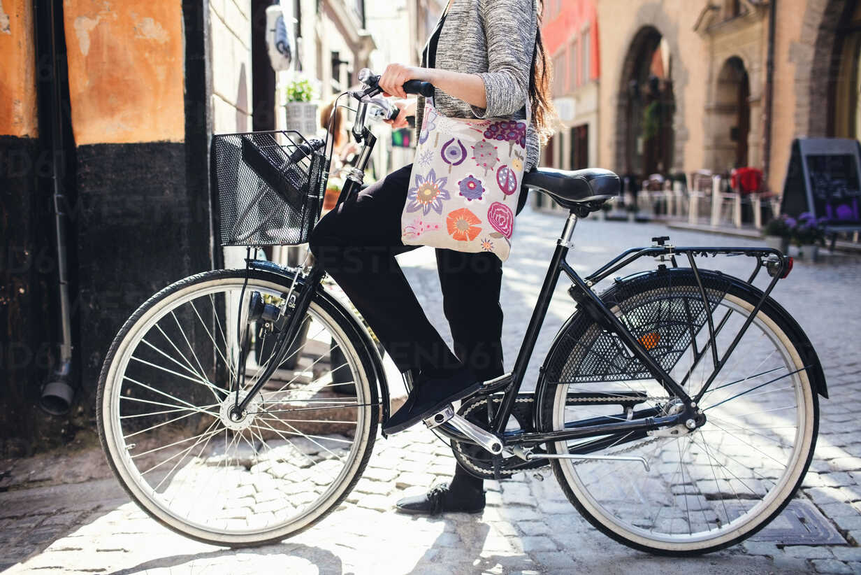 Low section of woman standing with bicycle on cobbled street - MASF03096 - Maskot ./Westend61