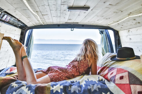 Rear view of woman lying on mattress in van while looking at view - CAVF36508