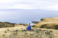 Rear view of woman sitting at Blowhole Beach - CAVF36517