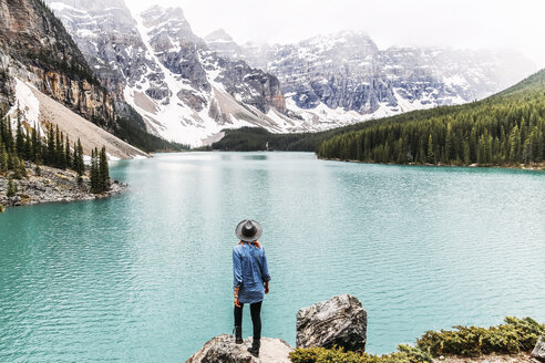 Rear view of woman in hat looking at view while standing on rock by Moraine Lake at Banff National Park - CAVF36547