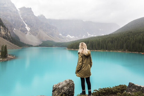 Rear view of female hiker with hand in pocket standing by Moraine Lake against mountains at Banff National Park - CAVF36565