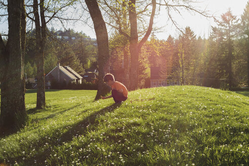 Side view of boy crouching on grassy field during sunny day - CAVF36574