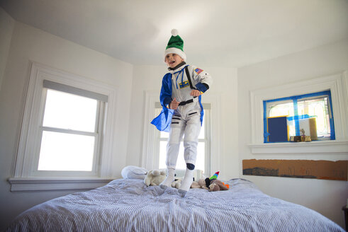 Happy boy wearing costume and jumping on bed at home - CAVF36616