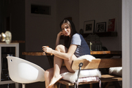 Low angle view of woman sitting on chair with coffee cup - CAVF36628