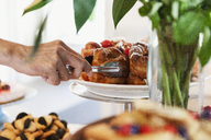 Cropped image of hand arranging desert on cakestand at cafe - MASF03136