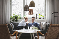 Couple looking in smartphone while sitting on sofa at home - MASF03139