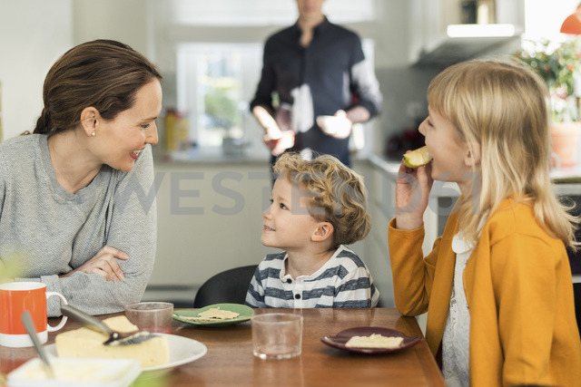 Family eating breakfast at dining table in living room - MASF03145