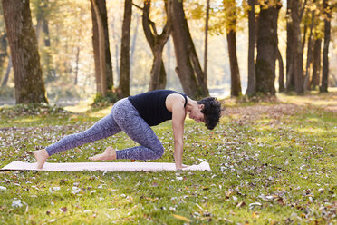 Mid adult woman in forest practicing yoga, climber exercise - SHOF00003