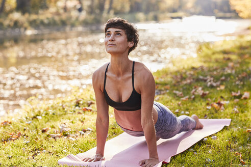 Mid adult woman in forest practicing yoga, cobra pose - SHOF00015