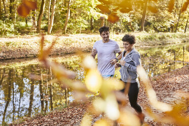 Couple jogging on autumnally forest track - SHOF00018