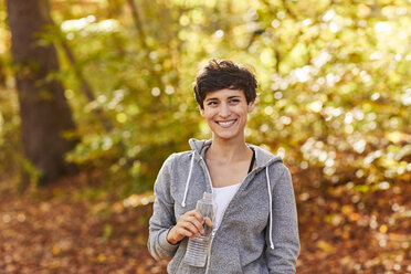Smiling female jogger with water bottle - SHOF00024